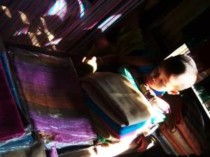 Bambino tra stoffe e telai in un villaggio galleggiante sul Mekong